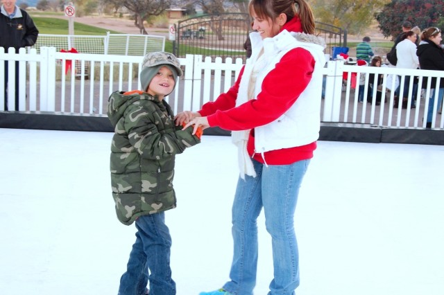From left, James Barrish, 7, receives help ice skating from his mother, Justine Barrish, at Family and Morale, Welfare and Recreation's Night of Extraordinary Lights Dec. 13 at Mountain View Golf Course. As an alternative to real ice, the rink was made of a synthetic material.