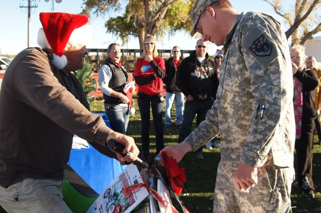 """From left, James Thomas, Family and Morale, Welfare and Recreation special events coordinator, holds the """"Toy Under the Tree"""" dirt bike as Pvt. Samual Atchley, Company C, 305th Military Intelligence Battalion, opens the lock and wins the giveaway. Atchley won the Kawasaki KLX 140 ADF dirt bike, valued at $2,999 during FMWR's Night of Extraordinary Lights on Saturday."""