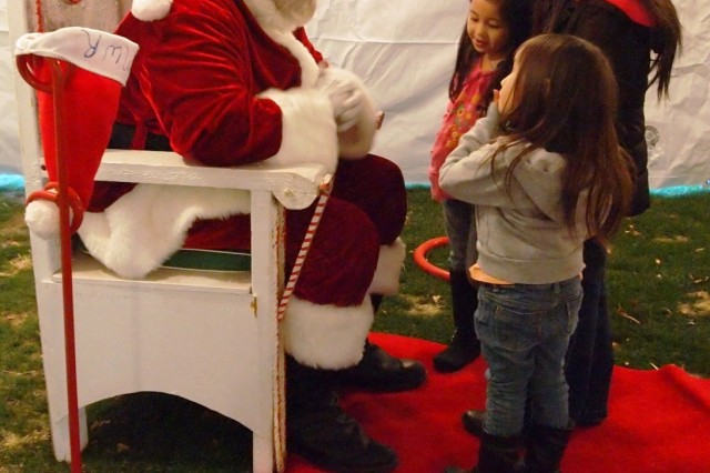 Pictured from front to back, sisters Janie, 4, Jennalyn, 8, and Rorie Gangcuangco, 6, visit with Santa Claus during Family and Morale, Welfare and Recreation's Night of Extraordinary Lights Dec. 13 at Mountain View Golf Course. Besides visiting Santa, children had the opportunity to write him a letter.