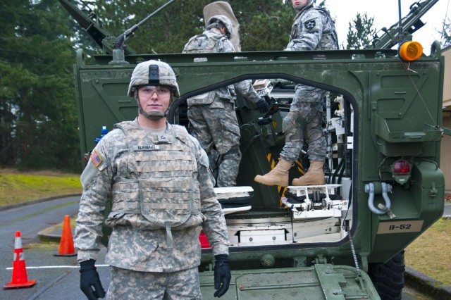 Pfc. Kyle Blignaut, a Lafayette, Ind., native, and assistant mortar gunner with Company B, 1st Battalion, 17th Infantry Regiment, 2-2 Stryker Brigade Combat Team, 7th Infantry Division, poses in front of a M1129 Mortar Carrier Vehicle during a virtual situational training exercise at Joint Base Lewis-McChord, Wash., Dec. 12. Blignaut was part of a mortar crew that supported the exercise by processing simulated fire missions in support of Soldiers who were executing the lane. (Photo by Staff Sgt. Bryan Dominique, 2-2 Stryker Brigade Combat Team, 7th Infantry Division)