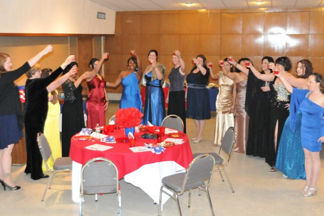"""The women of the 1st Battalion, 14th Field Artillery Family Readiness Group toast one another following a Molly Pitcher punch ceremony. A Battery and 578th Forward Support Company FRGs hosted a """"Wonder Woman"""" ball Dec. 13 to celebrate the hard work of their volunteers who have supported the battalion's deployed Soldiers."""