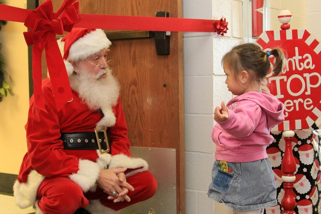 Santa ducks down under the ribbon to be cut at the ribbon-cutting for the Toys for Kids distribution center opening Dec. 16 to chat with Khloe Jernigan, 2. Toys for Kids is open today and Dec. 20 from 10 a.m. to 3 p.m. at the RecPlex, 2502 Sheridan Road.
