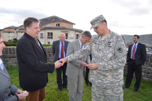 Col. William Bailey, 409th Contracting Support Brigade commander, presents Government Second Secretary of the BAAINBw, Rolf Schmitt, a commander's coin for his work and assistance during a key leader visit to the German Federal Army Procurement Office in Koblenz, Germany.