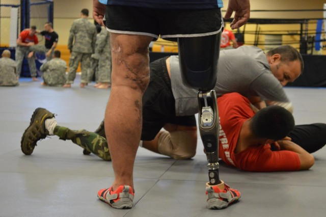 Sgt. Kristian Cedeno, Headquarters and Headquarters Company, Warrior Transition Unit, 3rd Infantry Division, watches as Rick Cicero attempts to pin Spc. Carlos Dieguez to the mat.