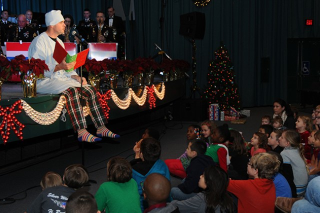 """Sgt. James Old, 98th Army """"Silver Wings"""" Band vocalist, reads """"'Twas the Night Before Christmas"""" to children in the post theater during the Commanding General's Holiday Concert Dec. 10."""