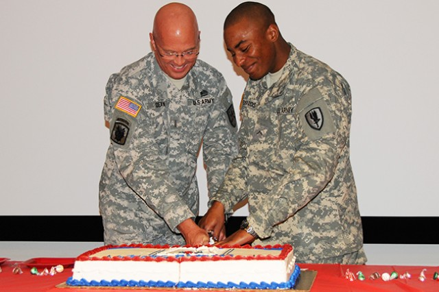 CW5 Max A. Dean, Warrant Officer Career College Army National Guard deputy commandant, and Pvt. Corey Edwards, A Company, 1st Battalion, 13th Aviation Regiment, cut a cake with a traditional sabre during the celebration of the 377th Army National Guard birthday in the regimental conference room of the USAACE Headquarters Dec. 13.