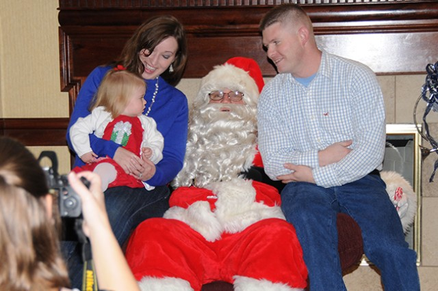 Second Lt. David Johnson, D Company, 1st Battalion, 145th Aviation Regiment, sits with his wife, Ashlee, and 18-month daughter, Sarah, as they take a photo with Santa at The Landing during Breakfast with Santa Dec. 14.