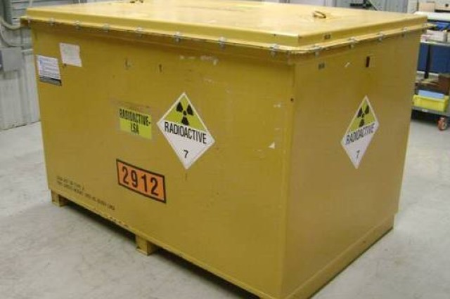 A heavy-gauge metal container, filled with low-level radioactive waste items, sealed for shipment.