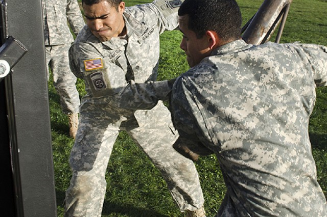 "Spcs. Moises Zamora (left) and Rafael Agosto dig deep to breach a steel door on Caserma Del Din Nov. 27 in the culminating event of the Sapper Stakes competition. Castle Company "" Company A, 173rd Brigade Special Troops Battalion, of the 173rd Infantry Brigade Combat Team (Airborne) "" put its combat engineers to the test at the end of November during the unit's first Sapper Stakes competition on both Caserma Del Din and Caserma Ederle in Vicenza, Italy."