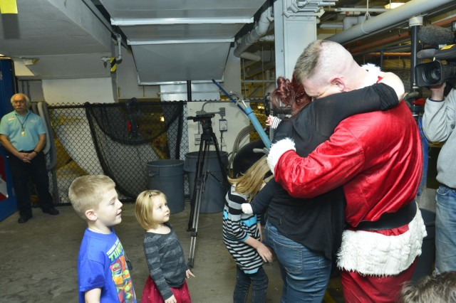 """First Lt. Nick Aldridge, executive officer with the Minnesota National Guard's 850th Horizontal Engineer Company, hugs his wife Brita when he surprised his family as """"Scuba Claus"""" at the Mall of America's Sea Life Aquarium in Bloomington, Minn., Dec. 22, 2013, after returning to the United States from a deployment to Afghanistan. The 850th repaired and maintained convoy and supply routes, cleared mine fields, improved drainage, deconstructed non-essential bases and built a resiliency center, a gym and multiple guard towers during their eight-month deployment to Afghanistan."""