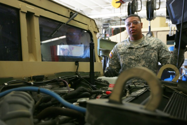 "Staff Sgt. Derrick Ivory, a vehicle mechanic in the U.S. Army Reserve, demonstrates proper maintenance inspection techniques during the filming of the Army's ""Defy Expectations"" advertising campaign."