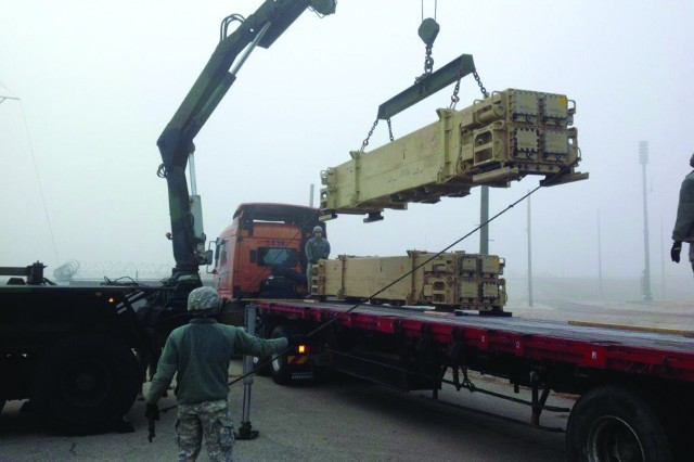 Soldiers with Battery A, 2-1 ADA load Patriot missiles onto a flatbed trailer using a guided missile transport crane at Kunsan Air Base, Dec. 5.