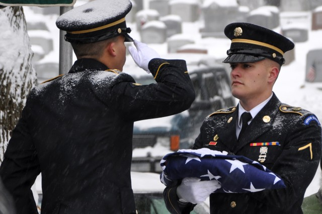 New York Army National Guard Spc. Christopher Roderiguez salutes the flag held by Pvt. Shelbi Vanderbogart as they complete folding the flag to be presented to the family of Army veteran Harold Smith during graveside services in Hudson, N.Y., Dec. 17, 2013. Smith's funeral was one of 9,735 that the New York Military Forces Honor Guard's 35 full-time and 135 part-time members performed for families across New York, as of Dec. 23.