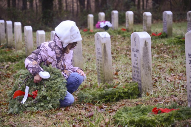 Samantha Manely, 6, reads the inscription on the headstone of Navy Lt. Cmdr. Julie A. Hall after placing a holiday wreath on her grave Dec. 14, 2013. Samantha and her Family took part in the Wreaths Across America ceremony at the Kentucky Veterans Cemetery-West, where attendees placed more than 1,900 holiday wreaths on gravesites thanks to donations made by the nonprofit agency and various local organizations.
