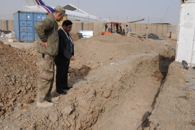 Lieutenant Commander Jared Asman (left), the Afghan Hand who serves as the KIA development advisor and Ahmadullah Faizi, the director of the Kandahar International Airport, discuss the construction progress of an improved septic system under construction at the airport. (U.S. Army photo by 1st Sgt. Mary L. Williams)