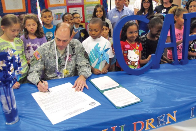 "SCHOFIELD BARRACKS, Hawaii "" Col. Daniel Whitney, commander, U.S. Army Garrison-Hawaii, helps Family Advocacy Committee members and children kick off Child Abuse Prevention Month by signing the CAPM Proclamation at the School Age Center, here, March 29."