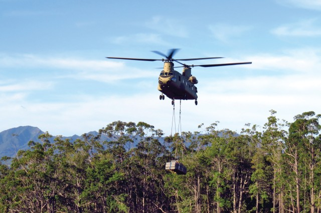 A CH-47 Chinook helicopter heads to the summits of the Ko'olau mountain range on Oahu, Hawaii, carrying a 1,000-pound sling-load of fencing material.