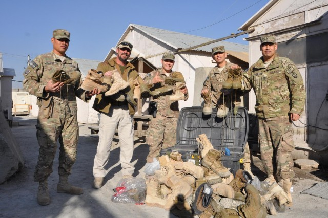 Patrick McCafferty (second from left) accepts more than 120 pairs of new and used boots from Task Force Guam, Dec. 25, 2013, as 1st Battalion, 294th Infantry Regiment, Guam Army National Guard, donated footwear to an Afghan security company headed by McCafferty. The Guam Soldiers performed this act of goodwill as their last Operation Enduring Freedom mission to the Afghanistan community. Shown are Staff Sgt. Erico Santos, McCafferty, Spc. James Esperon, Sgt. 1st Class Frank J. Limtiaco and Command Sgt. Maj. Mel Hennegan, Task Force Guam senior enlisted adviser, at Camp Phoenix, Kabul, Afghanistan.