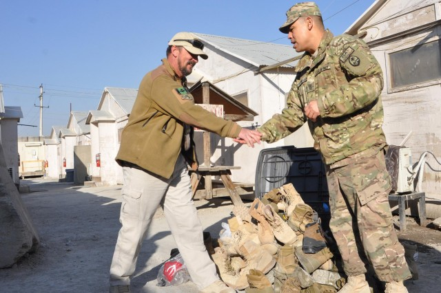 Command Sgt. Maj. Mel Hennegan, Task Force Guam senior enlisted adviser, acknowledges Patrick McCafferty after he accepted Guam's donation of 120-plus pairs of boots, Dec. 25, 2013, at Camp Phoenix, Kabul, Afghanistan. McCafferty received assistance from 1st Battalion, 294th Infantry Regiment, Guam Army National Guard, to outfit Afghan security guards.
