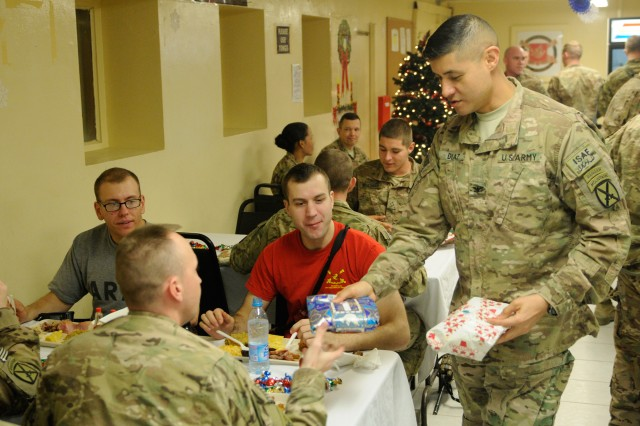"""LAGHMAN PROVINCE, Afghanistan """" U.S. Army Col. Mario Diaz, commander, 4th Brigade Combat Team, 10th Mountain Division, Task Force Patriot, hands out Christmas gifts to 5th Battalion, 25th Field Artillery Regiment Soldiers, Dec. 25, 2013, at Forward Operating Base Mehtar Lam's dining facility as they enjoy their Christmas dinner. Diaz spent his holiday getting out to visit his Soldiers across Regional Command-East, North of Kabul bringing them holiday cheer and seeing how they spent their Christmas. (U.S. Army Photo by Sgt. Eric Provost, Task Force Patriot PAO)"""