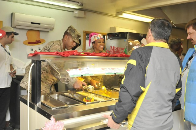 Task Force Lifeliner's Col. Charles R. Hamilton, a native of Houston, Texas, and commander of the 101st Sustainment Brigade, 101st Airborne Division (Air Assault), and Master Sgt. Katherine E. Lawson-Best, a native of New Orleans, La., and human resources administration noncommissioned officer in charge, serve meals during Christmas lunch, Dec. 25, 2013 at the Koele Dining Facility at Bagram Air Field, Parwan province, Afghanistan. As tradition has it, senior military leaders served their troops a feast worthy of the Holiday. (U.S. Army photo by Sgt. Sinthia Rosario, Task Force Lifeliner Public Affairs)