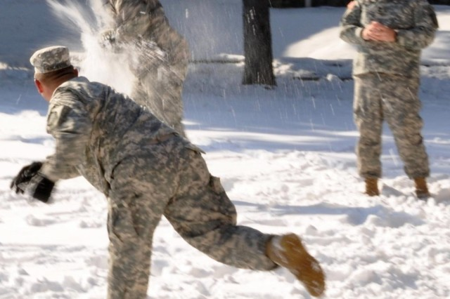 First Lt. Daniel Bodie, of Atlanta, explodes in a cloud of snow from a snowball thrown by 1st Sgt. Joshua Winchester, of Dublin, Ga.