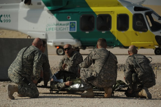 Soldiers ready the patient on the litter to transport him to the helicopter.