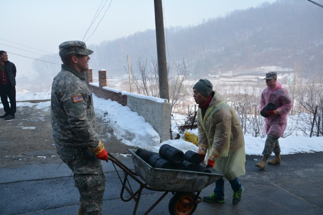 More than 70 Soldiers from 210th Field Artillery Brigade and 1st Armored Brigade Combat Team, 2nd Infantry Division, delivered charcoal briquettes to less fortunate families in Dongducheon, South Korea, to support a charity event sponsored by Gyeonggi Province, Dec. 18, 2013. They carried charcoal briquettes to needy family homes in Dongducheon Dec. 18.
