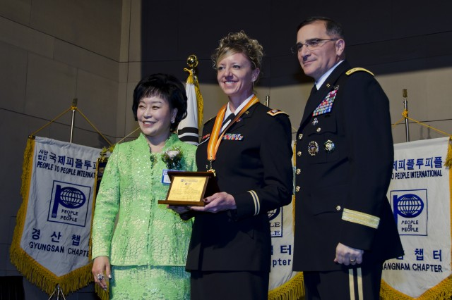 Servicemembers from across the peninsula were honored at the People to People International award banquet at the Grand Ballroom of the Grand Ambassador Hotel in Seoul, Dec. 20. Cpt. Amy Alexandra Rupert (center), adjutant assigned to 524th Military Intelligence Battalion, is flanked by Gen. Curtis M. Scaparrotti (right), United Nations Command, Combined Forces Command, United States Forces Korea commander, and Dr. Kim Gil Youn (left), chairwoman of PTPI Korea National Headquarters. The honorees were recognized for their community outreach, selfless service, volunteering time, and their commitment to a stronger U.S.-Korean friendship. (U.S. Army photo by Staff Sgt. Luke Graziani, USAG Yongsan Public Affairs Office)