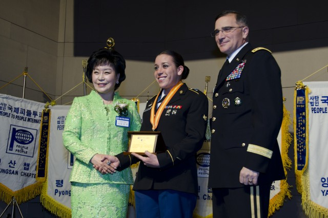 Servicemembers from across the peninsula were honored at the People to People International award banquet at the Grand Ballroom of the Grand Ambassador Hotel in Seoul, Dec. 20. Spc. Jessica McDonald, assigned to 2-2 Assault Battalion, is flanked by Gen. Curtis M. Scaparrotti (right), United Nations Command, Combined Forces Command, United States Forces Korea commander, and Dr. Kim Gil Youn (left), chairwoman of PTPI Korea National Headquarters. The honorees were recognized for their community outreach, selfless service, volunteering time, and their commitment to a stronger U.S.-Korean friendship. (U.S. Army photo by Staff Sgt. Luke Graziani, USAG Yongsan Public Affairs Office)