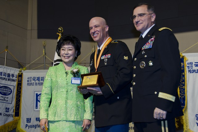 Servicemembers from across the peninsula were honored at the People to People International award banquet at the Grand Ballroom of the Grand Ambassador Hotel in Seoul, Dec. 20. Spc. Ronald Bunno, assigned to 2-2 Assault Battalion, is flanked by Gen. Curtis M. Scaparrotti (right), United Nations Command, Combined Forces Command, United States Forces Korea commander, and Dr. Kim Gil Youn (left), chairwoman of PTPI Korea National Headquarters. The honorees were recognized for their community outreach, selfless service, volunteering time, and their commitment to a stronger U.S.-Korean friendship. (U.S. Army photo by Staff Sgt. Luke Graziani, USAG Yongsan Public Affairs Office)