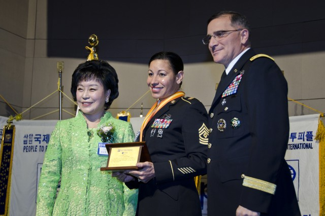 Servicemembers from across the peninsula were honored at the People to People International award banquet at the Grand Ballroom of the Grand Ambassador Hotel in Seoul, Dec. 20. First Sgt. Donna Swan, Headquarters and Headquarters Company 1st Sergeant, USAG Yongsan, is flanked by Gen. Curtis M. Scaparrotti (right), United Nations Command, Combined Forces Command, United States Forces Korea commander, and Dr. Kim Gil Youn (left), chairwoman of PTPI Korea National Headquarters. The honorees were recognized for their community outreach, selfless service, volunteering time, and their commitment to a stronger U.S.-Korean friendship. (U.S. Army photo by Staff Sgt. Luke Graziani, USAG Yongsan Public Affairs Office)