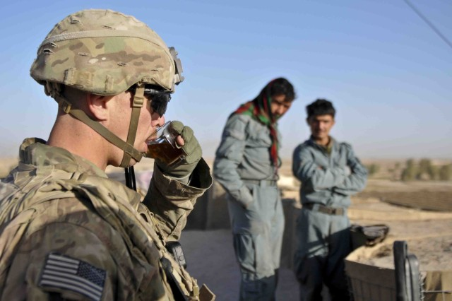 Staff Sgt. Jason Peacock with Troop O, 4th Squadron, Combined Task Force Dragoon, drinks chai tea with local Afghanistan Uniformed Police, Dec 17, 2013, in Kandahar Province, Afghanistan. The troopers conducted a series of patrol missions with the Afghanistan Uniformed Police at various security checkpoints throughout the province.