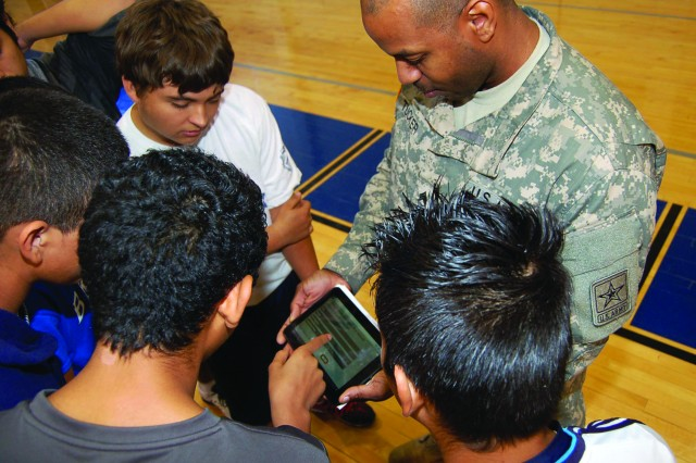 """Staff Sgt. Adrian Tucker displays a pad containing questions commonly found in standardized tests such as the Scholastic Aptitude Test and the Armed Services Vocational Aptitude Battery test.  Students were presented a question and then had to select the correct response from four potential answers. The Q & A was part of the strong mind """" strong body part of the iTeam Army Challenge."""