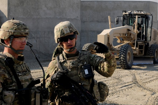 """LAGHMAN PROVINCE, Afghanistan """" U.S. Army Staff Sgt. Brandon Bleiler (right) of Kutztown, Pa., with the 333rd Engineer Company (Horizontal), and 1st Lt. Benedict Zilka (left), a native of Little Falls, Minn., with 284th Engineer Company (Vertical), discuss future engineer training and projects for Forward Operating Base Gamberi Jan. 5, 2014. Behind them, a 201st Afghan National Army soldier uses a grader to level out the area that will become the base's new expanded ammo control point. The ANA continually make efforts to expand their bases and their capabilities in preparation for protect their country during the upcoming elections. (U.S. Army Photo by Sgt. Eric Provost, Task Force Patriot PAO)"""
