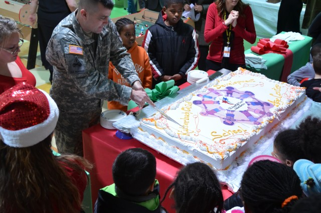 Col. Christopher M. Benson, U.S. Army Garrison Ansbach commander, cuts the cake during the grand opening of the Katterbach School Age Center and Child Development Center Dec. 16, 2013.