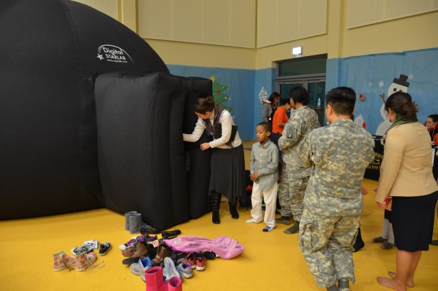 Attendees at the Katterbach School Age Center and Child Development Center grand opening Dec. 16 wait in line to see the inflatable planetarium in the gymnasium.