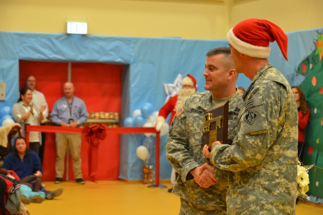 Col. D. Peter Helmlinger, right, commander of U.S. Army Corps of Engineers in Europe, hands Col. Christopher M. Benson, U.S. Army Garrison Ansbach commander, the key to the Katterbach School Age Center and Child Development Center during the grand opening of the joint facility Dec. 16, 2013.
