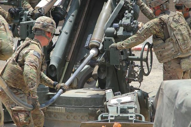 Soldiers from 3rd Platoon, Battery B, 4th Battalion, 320th Field Artillery Regiment, 4th Brigade Combat Team, 101 ABN DIV, 101st Airborne Division (Air Assault), load a 155mm High-Explosive round into a M777 howitzer during a fire mission in support of Easy Company, 2nd Battalion, 506th Infantry Regiment, out of Forward Operating Base Salerno, Afghanistan on June 11. (U.S. Army photo by Spc. Robert Porter)