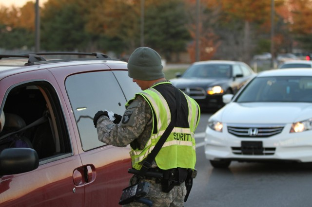 Spc. Bryan Clark, an infantryman from 1st Battalion, 187th Infantry Regiment, 3rd Brigade, 101st Airborne Division (Air Assault), checks identifications Dec. 12, at gate 4 on Fort Campbell. The gate guards help maintain security at the perimeter of the installation by diligently checking vehicles coming on post. (U.S. Army photo by Sgt. Leejay Lockhart, 101st Sustainment Brigade Public Affairs)