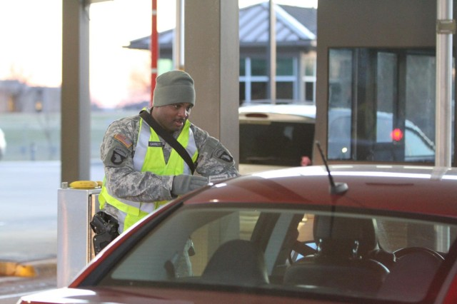 Sgt. Andre Garrett, a light wheel mechanic from Troop E, 2nd Squadron, 17th Cavalry Regiment, 101st Combat Aviation Brigade, 101st Airborne Division (Air Assault), checks identifications Dec. 12, at Fort Campbell's main gate. Garrett is one of 72 soldiers from the division who recently assumed the bulk of Fort Campbell's access control point mission. (U.S. Army photo by Sgt. Leejay Lockhart, 101st Sustainment Brigade Public Affairs)
