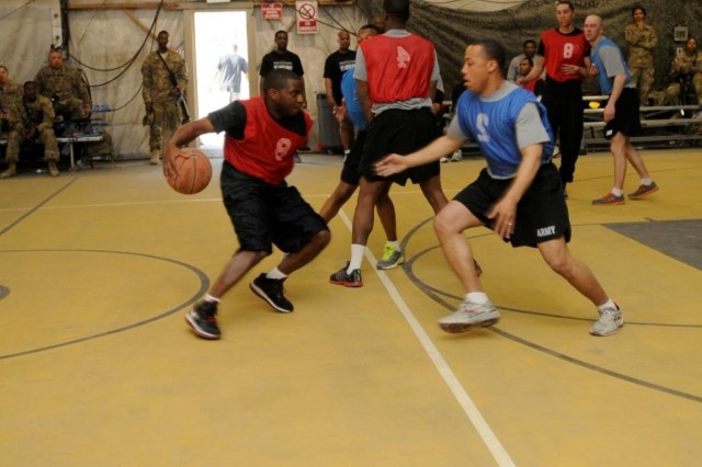 Sgt. Christopher A. Edwards, a native of Virginia Beach, Va., and help desk administrator with Task Force Lifeliner, dribbles a basketball during a game between officers and enlisted soldiers, Jan. 5, 2014, at Bagram Air Field, Parwan province, Afghanistan. During the game the officers wore blue jerseys and the enlisted wore red jerseys. (U.S. Army photo by Sgt. Sinthia Rosario, Task Force Lifeliners Public Affairs)