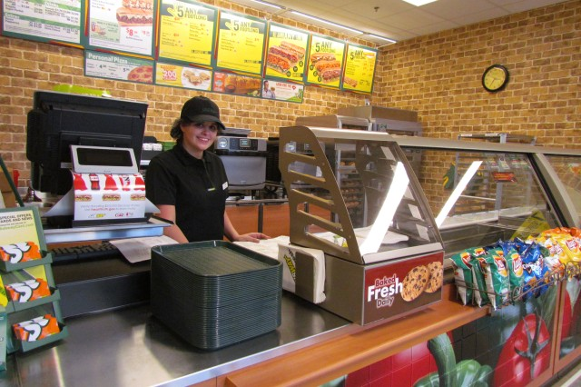 AAFES employee Kaitlyn Green is ready for opening day at the Subway sandwich shop at the Express convenience store and fast food shopping center.