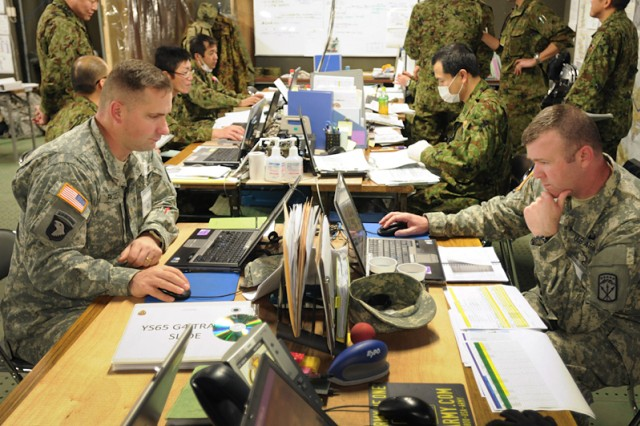 Maj. Charles Rozek (left), I Corps, and Sgt. 1st Class Otis Cadd, 593rd Expeditionary Sustainment Command, track and coordinate transportation of supplies and personnel during Yama Sakura 65, the 5-day bilateral military simulation exercise at Camp Higashi-Chitose located on the northern island of Hokkaido, Japan.