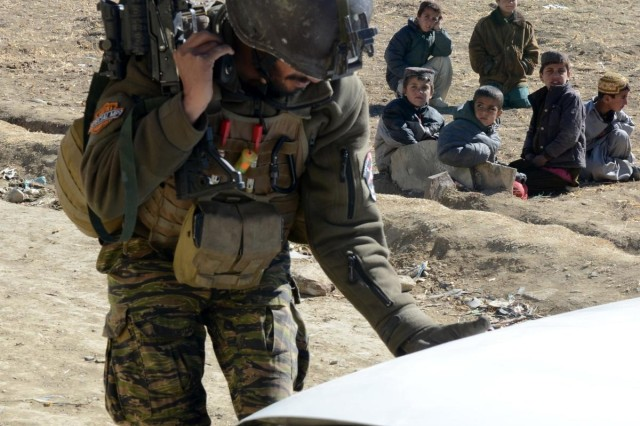 A Paktika village response unit member searches a vehicle during a clearing operation in Oazai village, Sar Houzah district, Paktika Province, Afghanistan, Jan. 5, 2014.