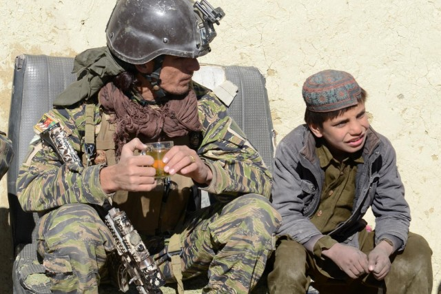 A village response unit member, or VRU, speaks with a child after a clearing operation in Oazai village, Sar Houzah district, Paktika Province, Afghanistan, Jan. 5, 2014. After the operation, the VRU commander stressed the importance of establishing an Afghan Local Police checkpoint in the village.