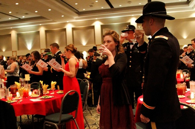 """Capt. Jordan Swears (right), a field artillery officer assigned to Headquarters and Headquarters Battery of the 1st """"Dragon"""" Battalion, 82nd Field Artillery Regiment, 1st """"Ironhorse"""" Brigade Combat Team, 1st Cavalry Division, and his wife, Sarah, an administrative assistant, drink to one of nine ceremonial toasts during the Dragon's Saint Barbara's Day Ball, recently, in Killeen, Texas. At the ball, Soldiers, spouses and distinguished guests dressed in their best and paid tribute to Saint Barbara, the patron saint of field artillery.  (U.S. Army photo by Pfc. Paige Pendleton, 1st BCT PAO, 1st Cav. Div.)"""