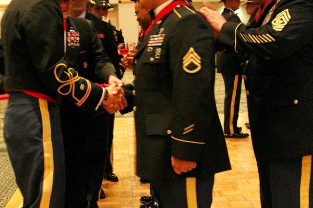 """Lt. Col. Richard Ng (left), commander of the 1st """"Dragon"""" Battalion, 82nd Field Artillery Regiment, 1st """"Ironhorse"""" Brigade Combat Team, 1st Cavalry Division, shakes the hand of Staff Sgt. Russell Sanchez, a Dragon field artillery automated tactical data systems specialist, while Command Sgt. Maj. Steven Rosales (right), Dragon command sergeant major, places the Honorable Order of Saint Barbara medal around his neck during the Dragon's Saint Barbara's Day Ball, recently, in Killeen, Texas. """"Every day I woke up and just tried to be the best I can to get there,"""" Sanchez said.  (U.S. Army photo by Pfc. Paige Pendleton, 1st BCT PAO, 1st Cav. Div.)"""