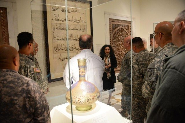 "Deniz Beyazit, an assistant curator with the Metropolitan Museum of Art, shows a group of 353d Civil Affairs Command Soldiers a folio from the ""Qu'ran of Umar Aqta"" during the unit's visit to the Metropolitan Museum of Art, Nov. 17, 2013, in New York."