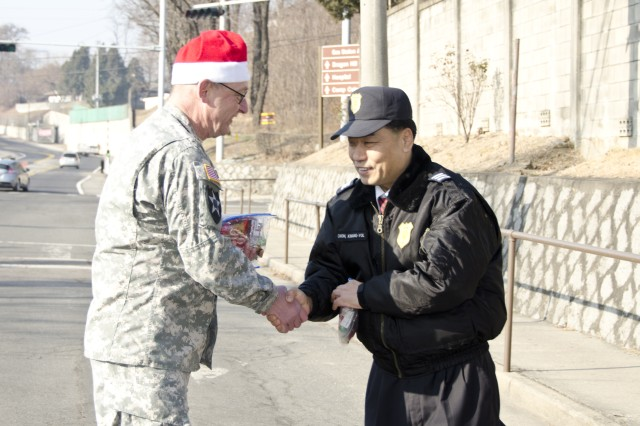 Command Sgt. Maj. Daniel Willing, command sergeant major for USAG Yongsan, during Operation Santa Express, thanks one of many security guards across Yongsan, for his dedication to duty during the holidays, Dec. 24. Operation Santa Express is an annual token of appreciation for all the first responders and security forces across Yongsan. (U.S. Army photo by Staff Sgt. Luke Graziani, USAG Yongsan Public Affairs Office)